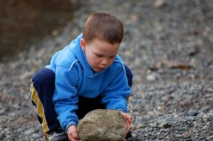 kid picking up big rock