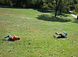 kids rolling on hill